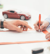 hands signing a document with new car in background