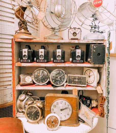 shelf of antique fans, cameras and clocks