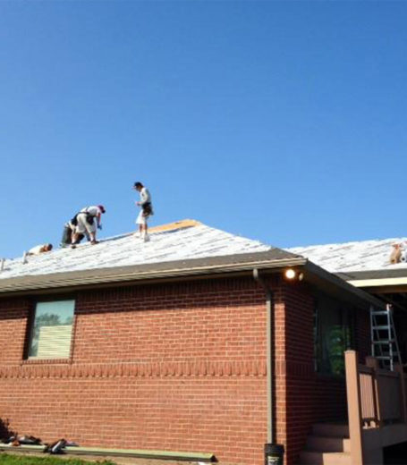 roofers working on top of a house